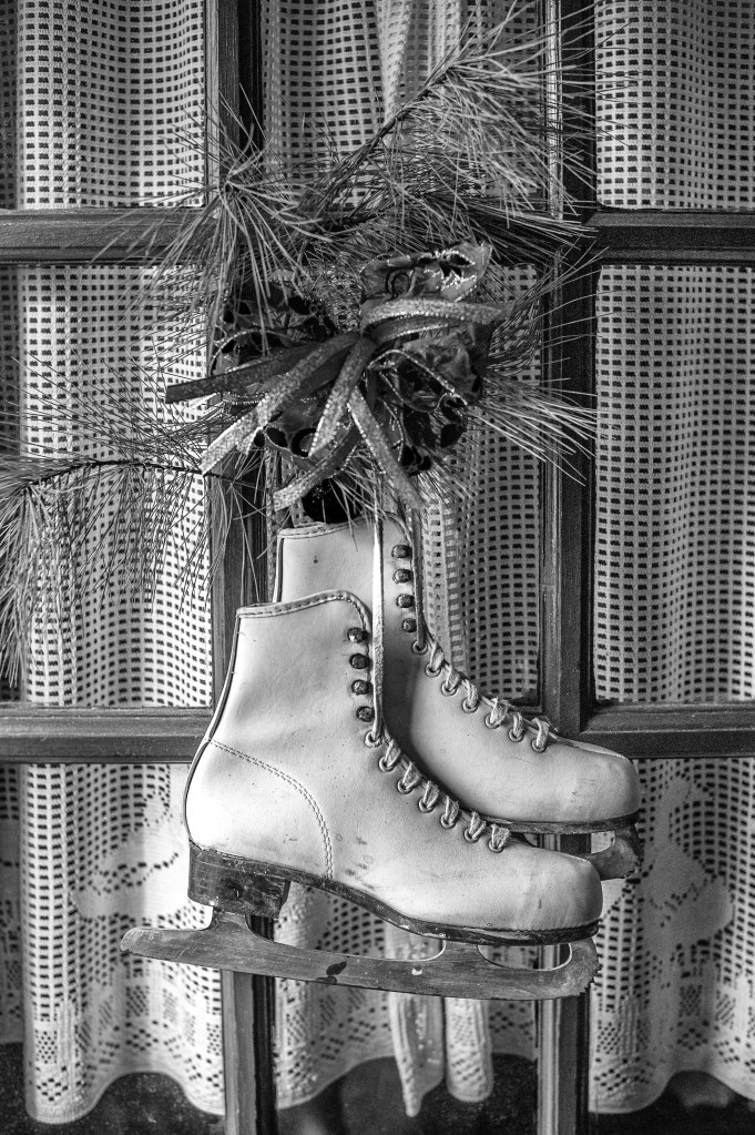 This is a pair of skates hanging on the back door.